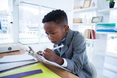 Le garçon imiting comme écriture d'homme d'affaires sur le papier a attaché au presse-papiers photo stock