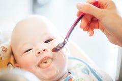Le garçon infantile d'enfant de bébé six mois mange Images stock