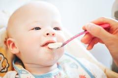 Le garçon infantile d'enfant de bébé six mois mange Image libre de droits