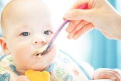 Le garçon infantile d'enfant de bébé six mois mange Photos libres de droits