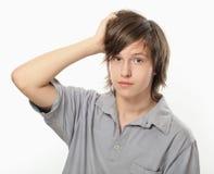 Le garçon jeune tient sa main à la tête Image libre de droits