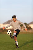 Le garçon jongle avec du ballon de football dehors Image libre de droits