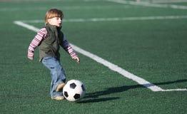 Le garçon jouant au football Photos stock