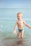 Le garçon jouant avec l'eau et lui aime faire le jet Image libre de droits