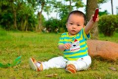 Le garçon jouant dans le couteau militaire suisse sur la pelouse Photos stock