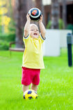 Le garçon joue au football en parc images stock