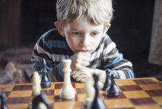 Le garçon joue aux échecs Photo stock