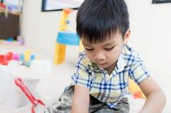 Le garçon joue avec des jouets de bac à sable dans le terrain de jeu éducatif photographie stock