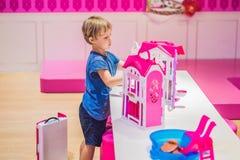 Le garçon joue avec des jouets et des poupées de fille photo libre de droits