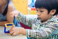 Le garçon joue avec le jouet d'éducation dans la salle de classe Photos stock