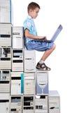 Le garçon joue avec l'ordinateur portatif des opérations à partir de vieux ordinateurs Image libre de droits