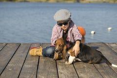 Le garçon joue avec son chien Photographie stock libre de droits