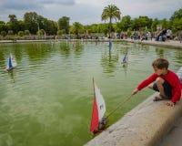 Le garçon joue avec un voilier à l'étang aux jardins du luxembourgeois Photo stock