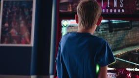 Le garçon joue dans le hall des machines à sous dans un jeu vidéo Amusement grand Communication d'enfant banque de vidéos