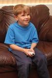 Le garçon joue heureusement le jeu vidéo Photographie stock libre de droits