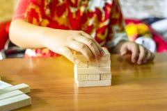 Le garçon joue le jeu de pile de blocs en bois par sa main Concept d'affaires photos libres de droits