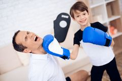 Le garçon joue la boxe avec son père images libres de droits
