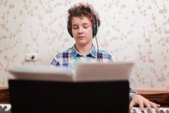Le garçon joue le piano images libres de droits