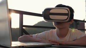 Le garçon joue sur l'ordinateur en verres de réalité virtuelle dans le coucher du soleil au coucher du soleil Le concept de moder clips vidéos