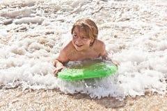 Le garçon a l'amusement avec la planche de surfing Photographie stock libre de droits