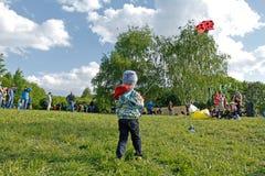 Le garçon lance le cerf-volant de coccinelle dans le ciel au festival de cerf-volant en parc Tsaritsyno à Moscou Images stock