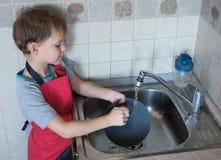 Le garçon lave des plats Image stock