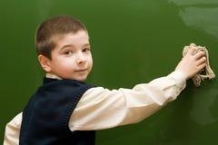 Le garçon lave un tableau noir Image libre de droits