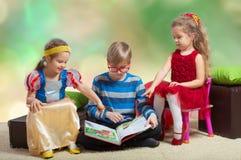 Le garçon lit un livre à de petites filles Photos libres de droits