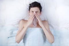 Le garçon malade, adolescent a attrapé froid, se situant dans le lit, haute température, alitement, mal de tête, santé pauvre image stock