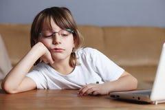 Le garçon malheureux s'assied devant son ordinateur portatif Photos libres de droits