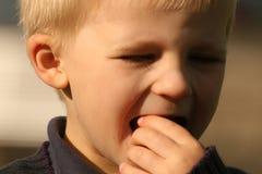 Le garçon mange à la lumière du soleil lourde Image stock