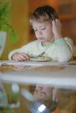 Le garçon mange à la table Photographie stock libre de droits