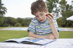 Le garçon mange Apple tout en lisant dehors Photos stock
