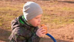 Le garçon mange des gaufres se reposant sur le banc en parc clips vidéos