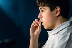 Le garçon mange du maïs éclaté au cinéma Image stock