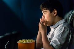 Le garçon mange du maïs éclaté au cinéma Images libres de droits
