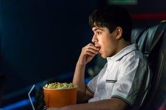 Le garçon mange du maïs éclaté au cinéma Photos libres de droits