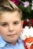 Le garçon mange la crème glacée, fleurs à l'arrière-plan Images libres de droits