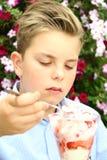 Le garçon mange la crème glacée, fleurs à l'arrière-plan Photo libre de droits