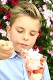 Le garçon mange la crème glacée, fleurs à l'arrière-plan Images stock