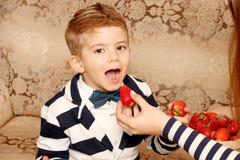 Le garçon mange les fraises savoureuses Images libres de droits