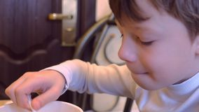 Le garçon mange les nouilles instantanées se reposant sur le lit dans la pension banque de vidéos