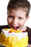 Le garçon mange un gâteau savoureux Photos stock