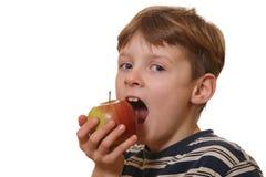 Le garçon mange une pomme photos libres de droits