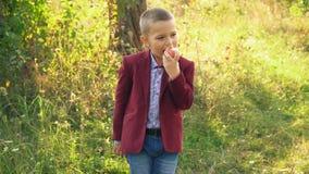 Le garçon mange une pomme