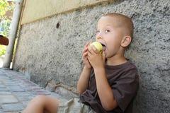 Le garçon mange une pomme Images stock