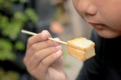 Le garçon mangeant du pain grillé a complété avec les amandes et le miel Image libre de droits