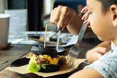 Le garçon mangeant du porc noir d'hamburger du plat sur une étiquette en bois image libre de droits