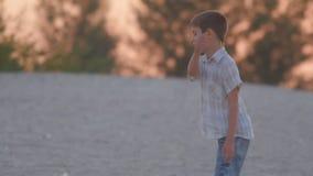 Le garçon marche le long de la plage au coucher du soleil Reste actif de l'enfant banque de vidéos