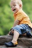 Le garçon mignon apprécie le jour ensoleillé à la cour de jeu. Image stock